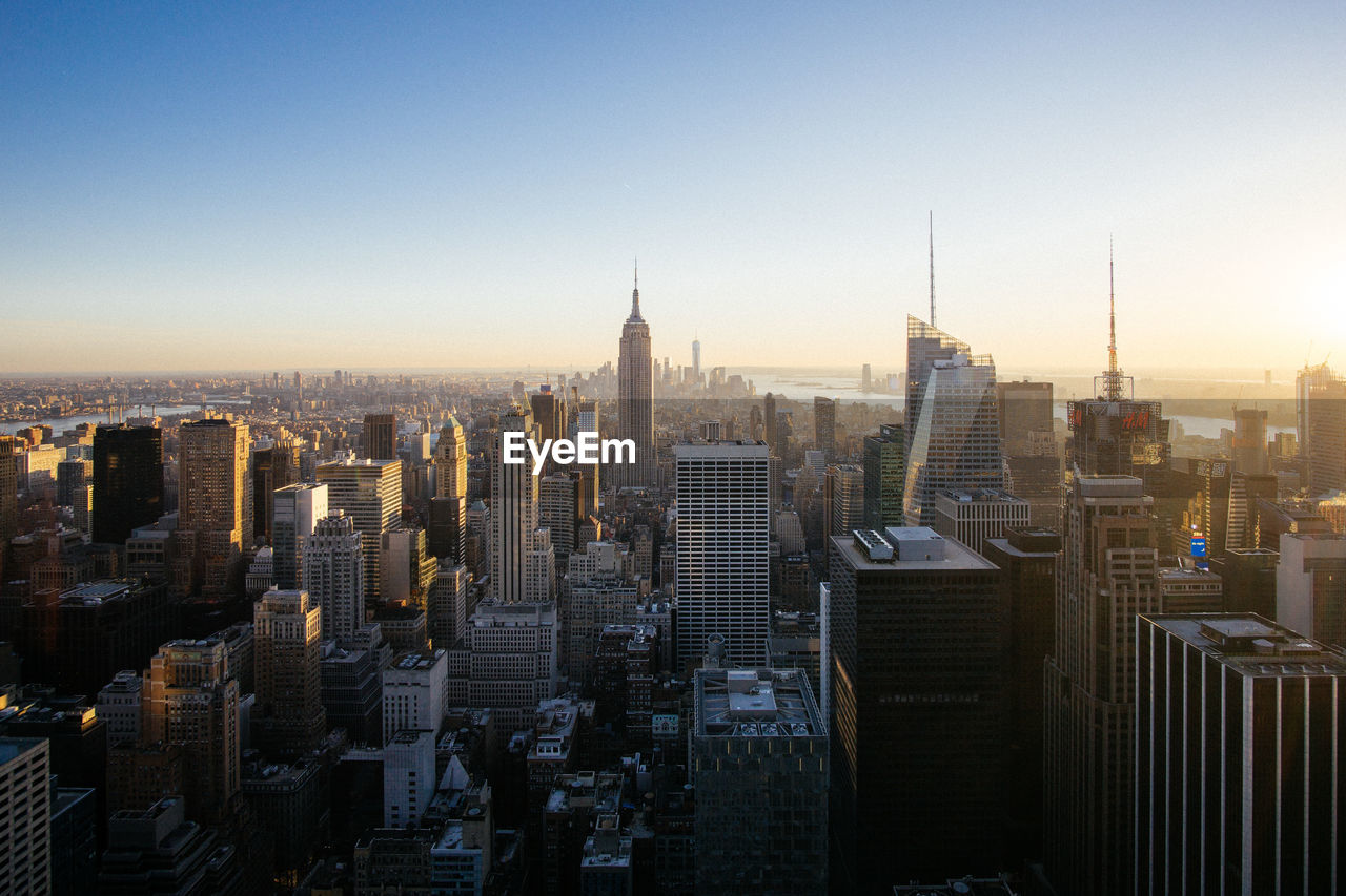 High angle view of cityscape with empire state building against clear sky during sunset