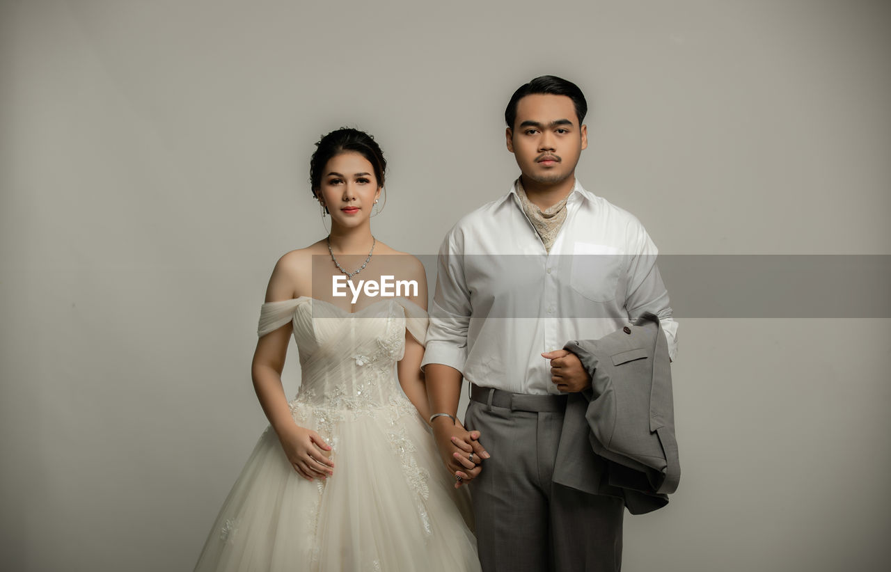 PORTRAIT OF A YOUNG COUPLE STANDING AGAINST WALL