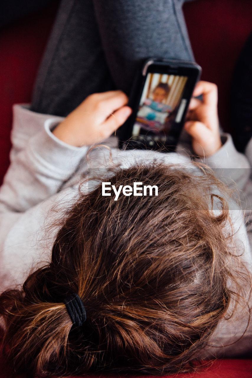 High Angle View Of Girl Using Mobile Phone