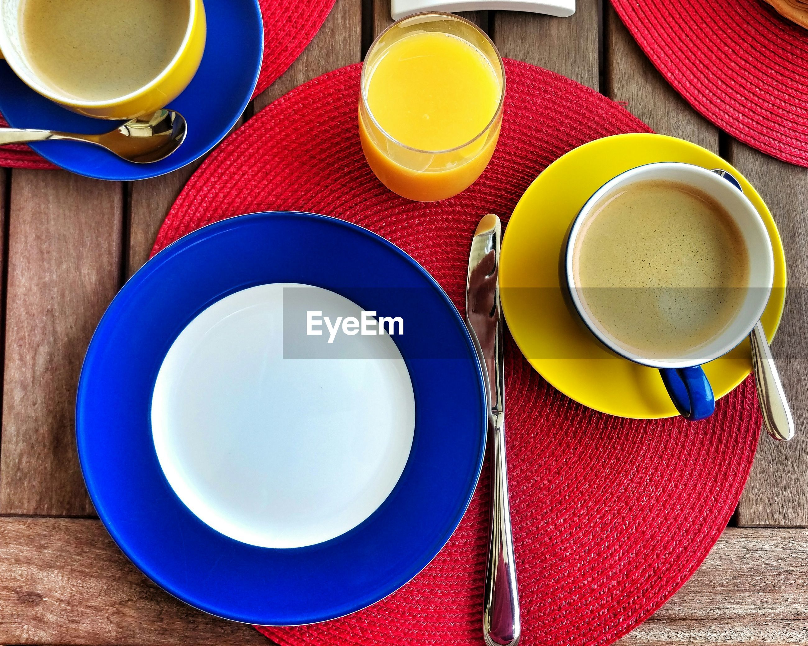 Directly above shot of empty plate by coffee and orange juice on table