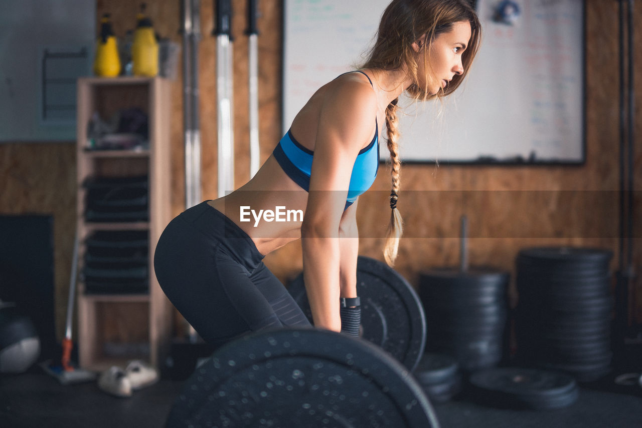 exercising, real people, gym, one person, lifestyles, strength, indoors, young women, focus on foreground, young adult, leisure activity, sports clothing, health club, exercise equipment, beautiful woman, sport, day, full length, athlete, people