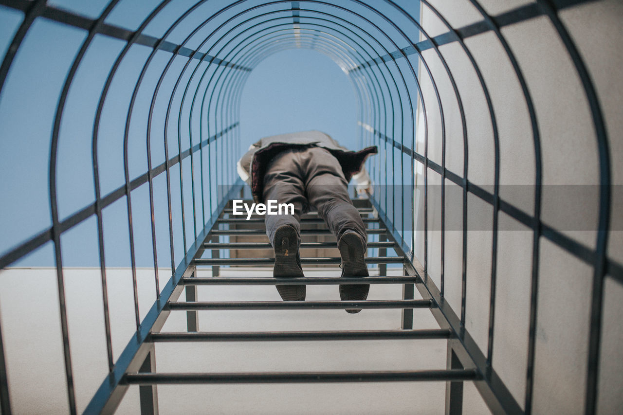 Low angle view of man standing on ladder against sky