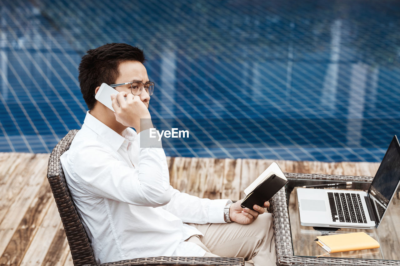 Man talking on phone while sitting against swimming pool