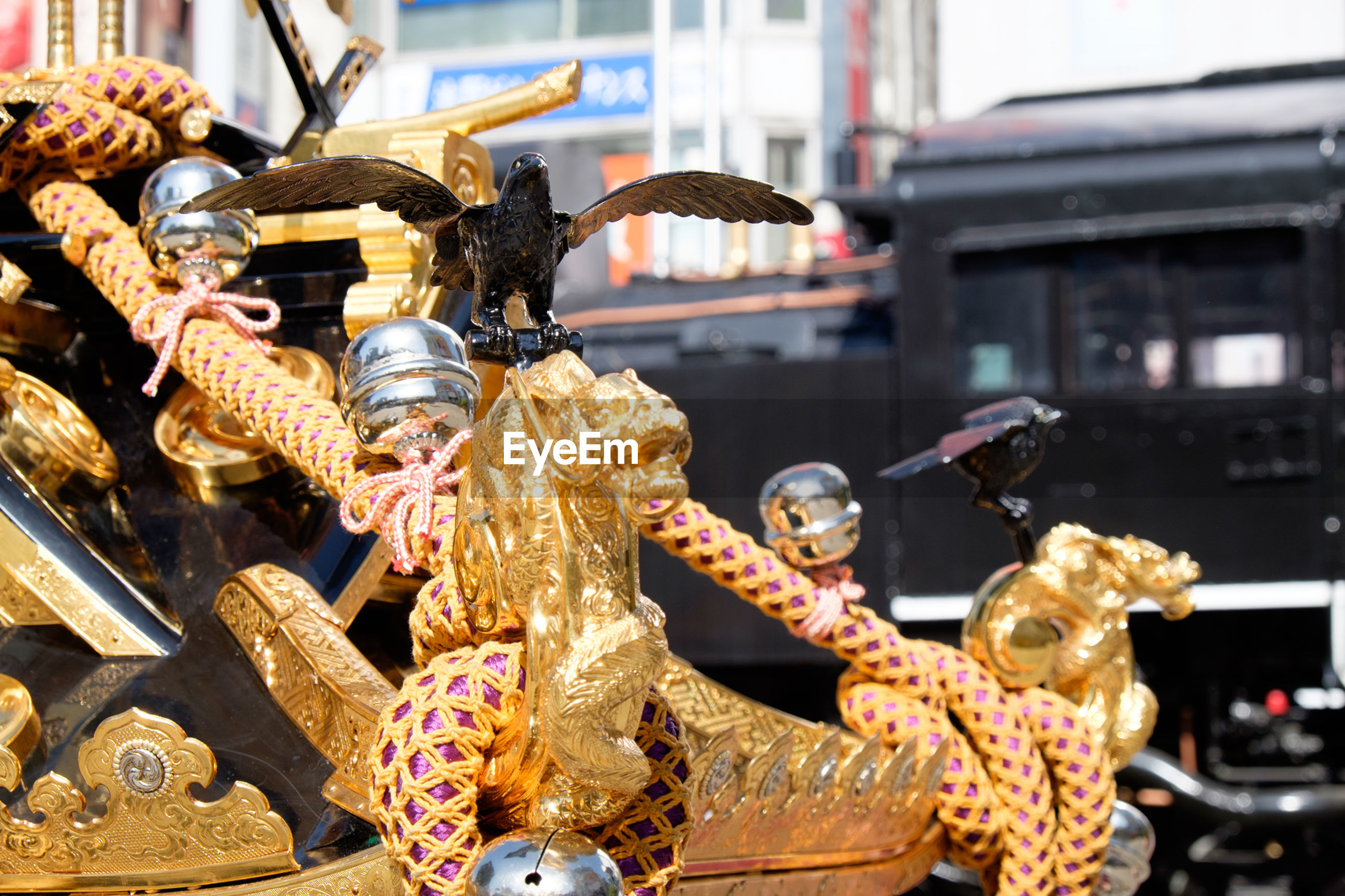 Close-up of golden statues against buildings in city