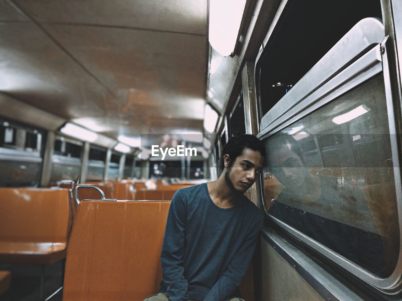 Thoughtful young man sitting by window while traveling in train