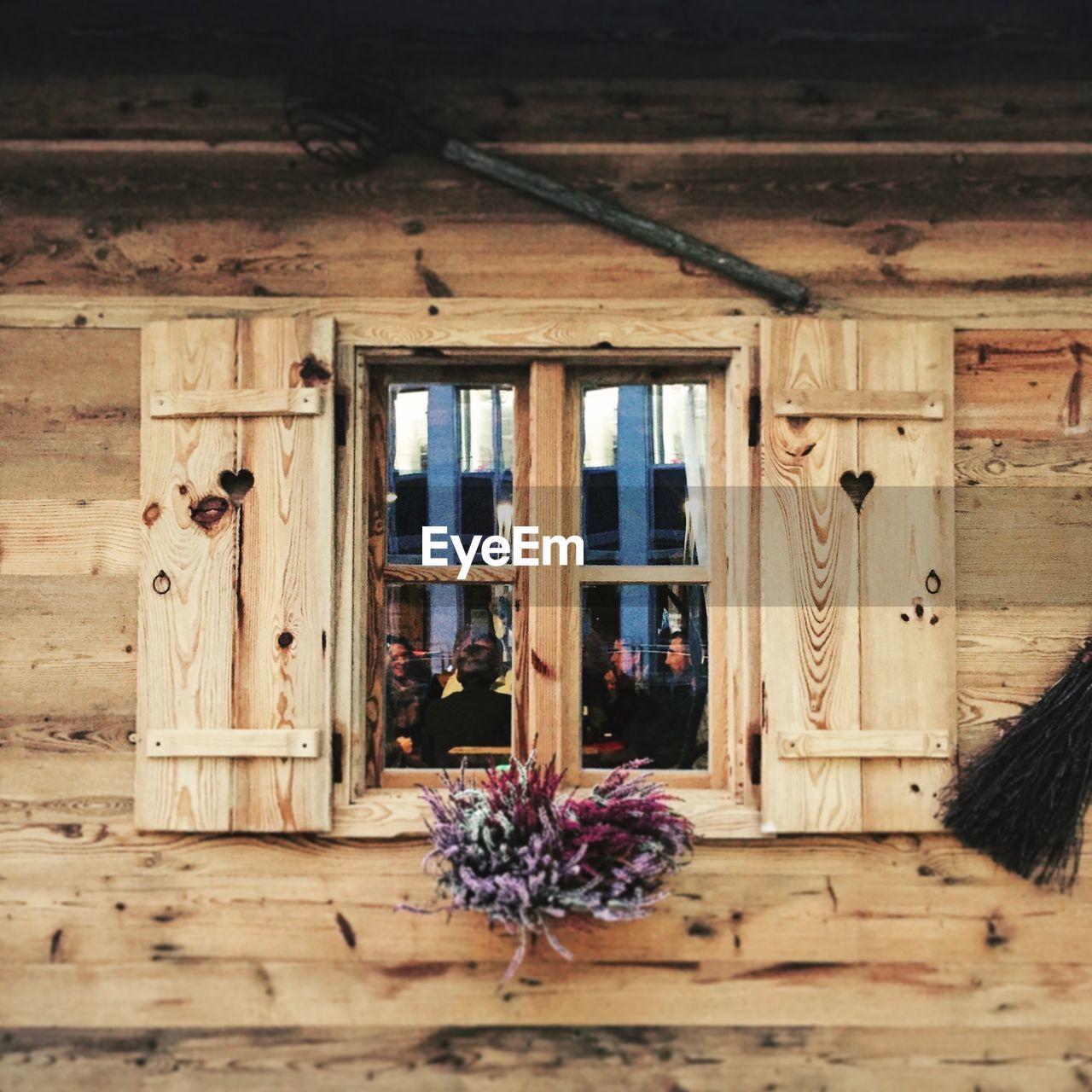 Bunch Of Flowers On Window Of Log Cabin