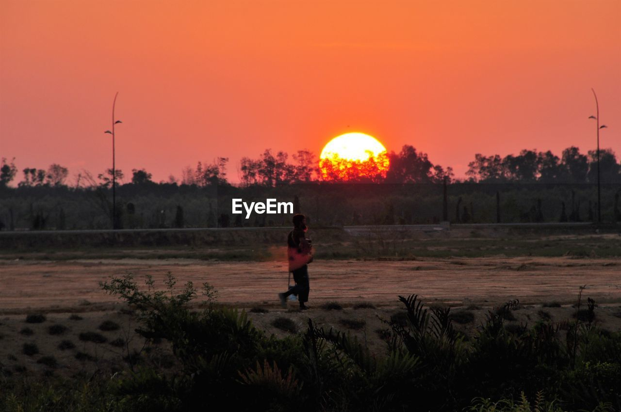 sunset, real people, field, sun, full length, nature, one person, outdoors, leisure activity, beauty in nature, sky, tree, standing, ball, scenics, lifestyles, alternative energy, landscape, windmill, clear sky, technology, wind turbine, wind power, industrial windmill, day, mammal, people