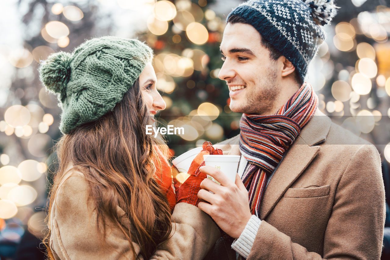 Close-Up Of Smiling Couple Holding Coffee Cup During Winter