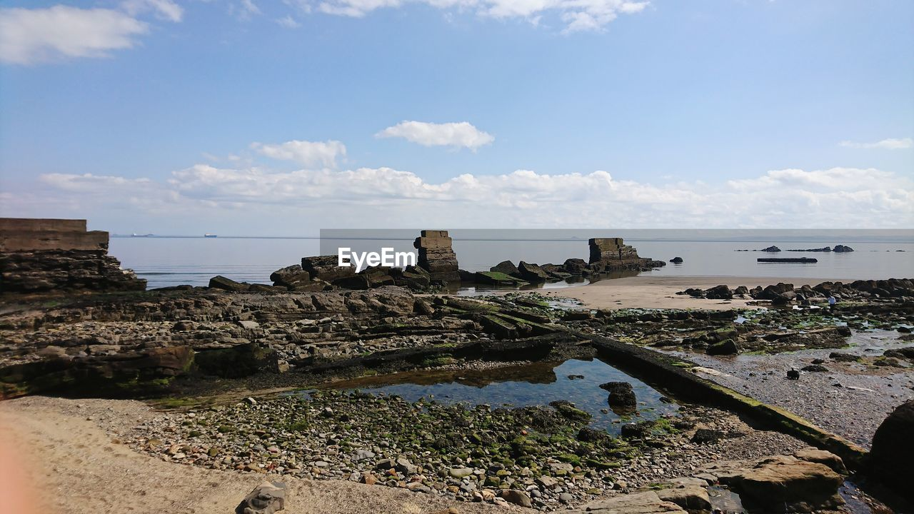 sky, water, sea, nature, cloud - sky, day, architecture, land, beach, scenics - nature, tranquil scene, no people, beauty in nature, rock, tranquility, built structure, outdoors, solid, history, ruined, ancient civilization