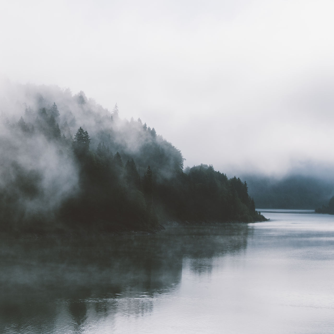 water, sky, scenics - nature, beauty in nature, no people, tranquility, tranquil scene, smoke - physical structure, nature, waterfront, non-urban scene, day, lake, cloud - sky, tree, environment, outdoors, plant, pollution, power in nature, air pollution