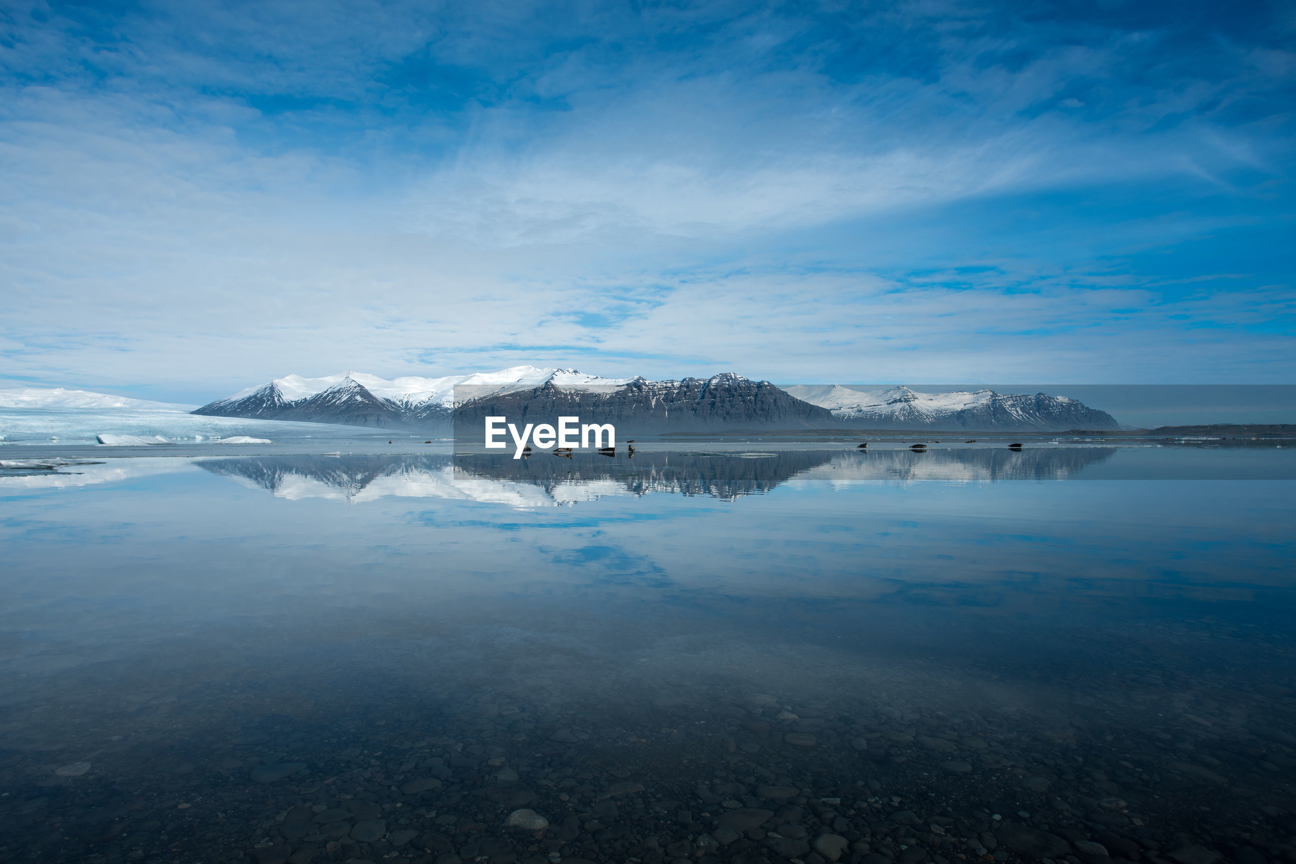 Scenic view of sea by mountains against blue sky during winter