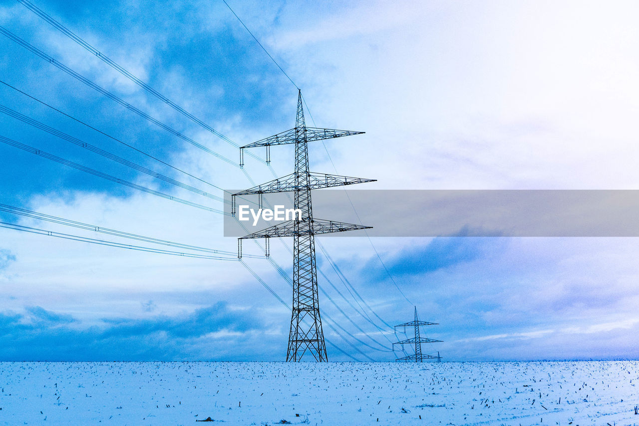 cloud - sky, sky, technology, electricity, cable, electricity pylon, connection, nature, power line, no people, power supply, fuel and power generation, low angle view, day, snow, beauty in nature, winter, cold temperature, outdoors, electrical equipment