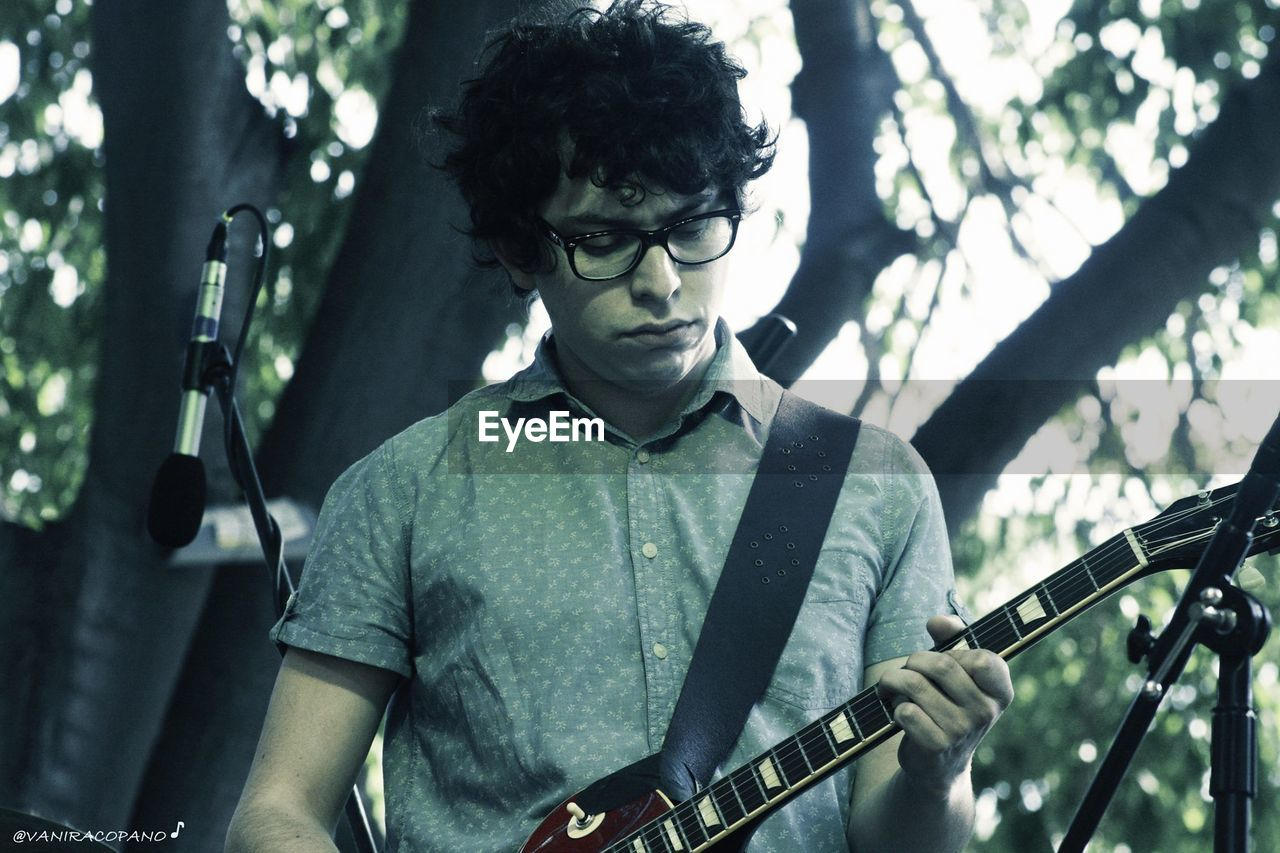 music, musical instrument, guitar, arts culture and entertainment, casual clothing, one person, real people, playing, front view, young adult, focus on foreground, musician, performance, lifestyles, eyeglasses, portrait, young men, leisure activity, outdoors, day, electric guitar, rock music, rock musician, people