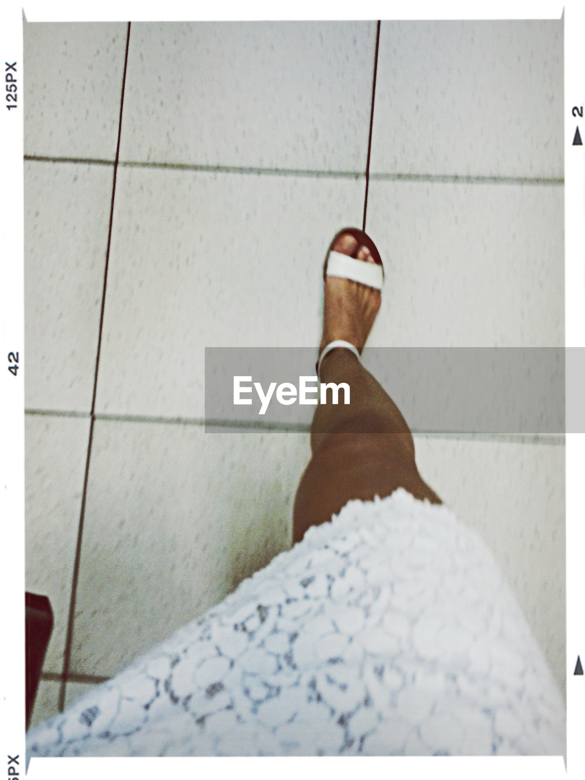 tiled floor, low section, transfer print, shoe, flooring, person, tile, auto post production filter, indoors, footwear, white color, high angle view, wall - building feature, floor, sidewalk, standing, shadow, personal perspective