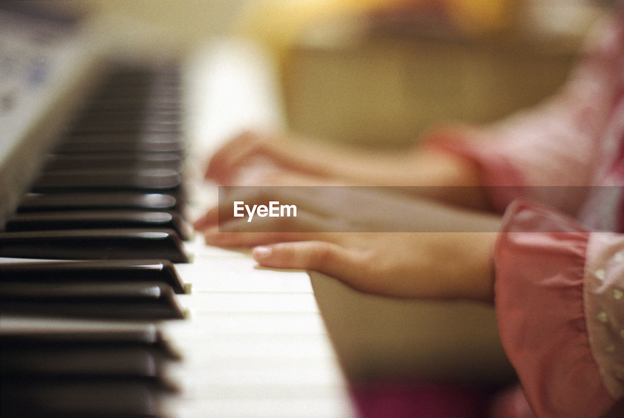 CLOSE-UP OF HANDS PLAYING PIANO AT HOME