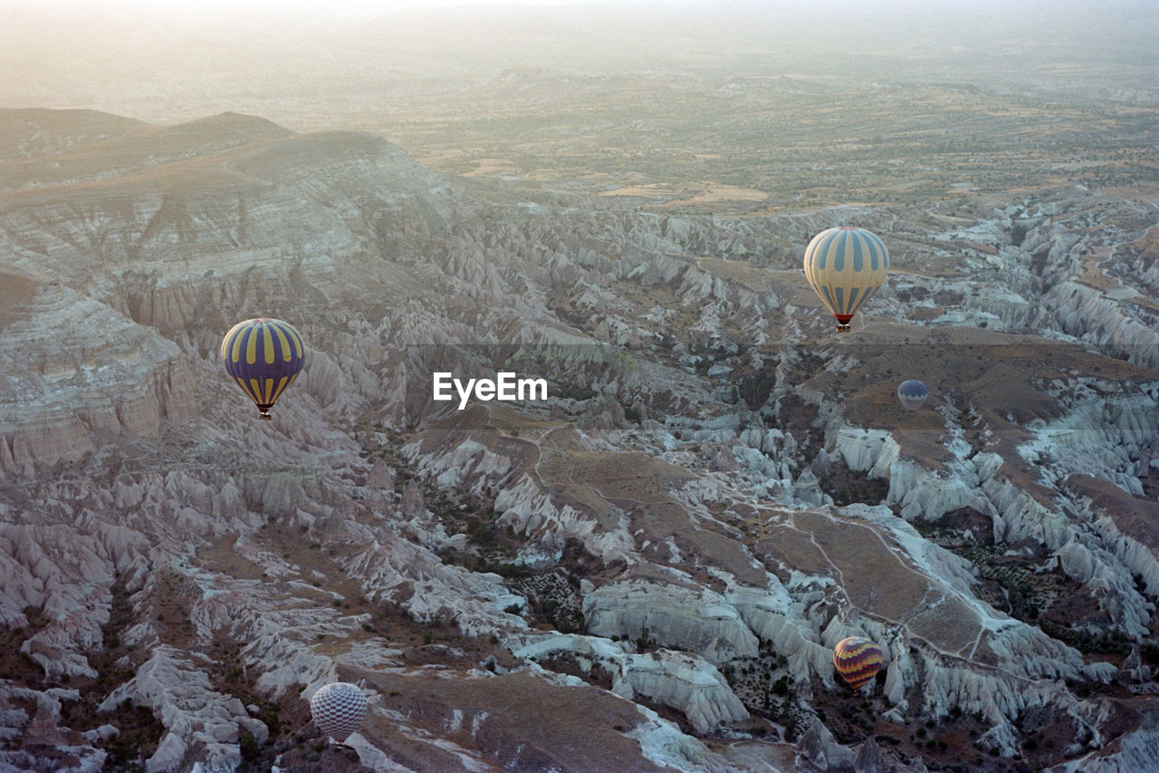 hot air balloon, air vehicle, flying, mountain, balloon, mid-air, adventure, transportation, scenics - nature, mode of transportation, landscape, non-urban scene, travel, beauty in nature, nature, day, environment, tranquil scene, rock, rock formation, no people, ballooning festival, outdoors