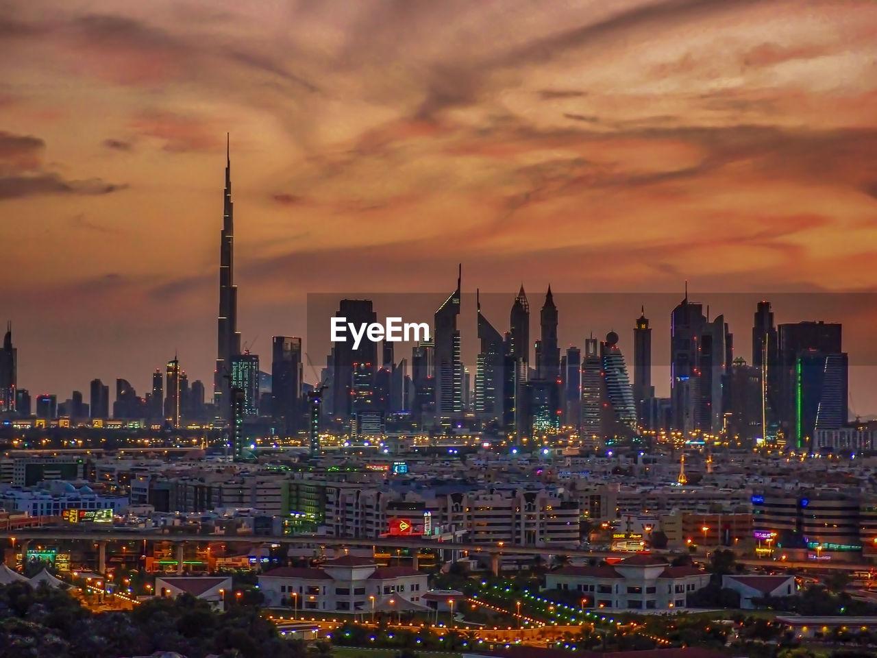 Illuminated Cityscape Against Dramatic Sky During Sunset