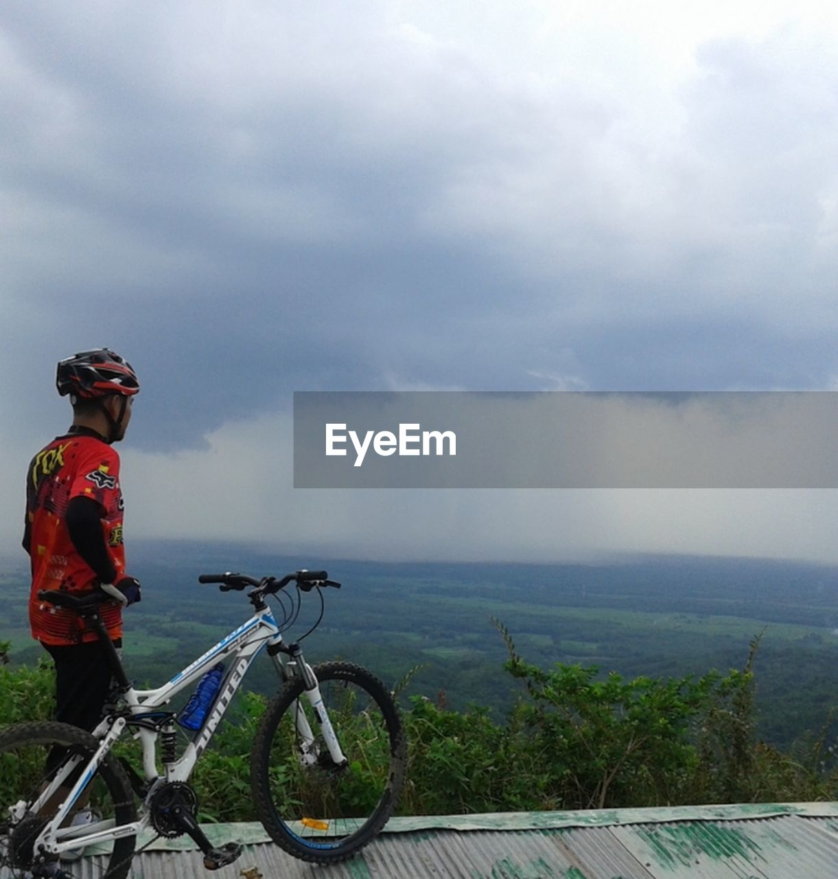 sky, bicycle, transportation, cloud - sky, mode of transport, day, nature, outdoors, real people, cycling helmet, scenics, cycling, water, one person, sea, adventure, horizon over water, land vehicle, beauty in nature, mountain bike, landscape, men, lifestyles, headwear, mountain, people