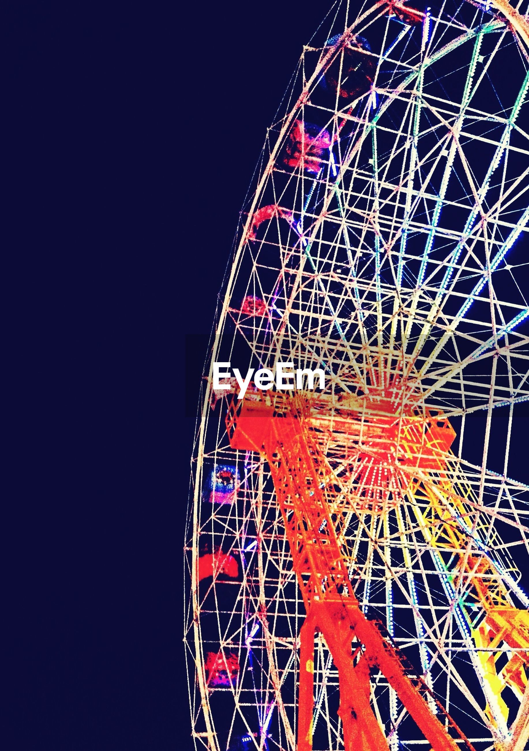 amusement park, amusement park ride, ferris wheel, arts culture and entertainment, low angle view, illuminated, night, clear sky, metal, fun, sky, blue, built structure, copy space, traveling carnival, multi colored, outdoors, no people, circle, enjoyment