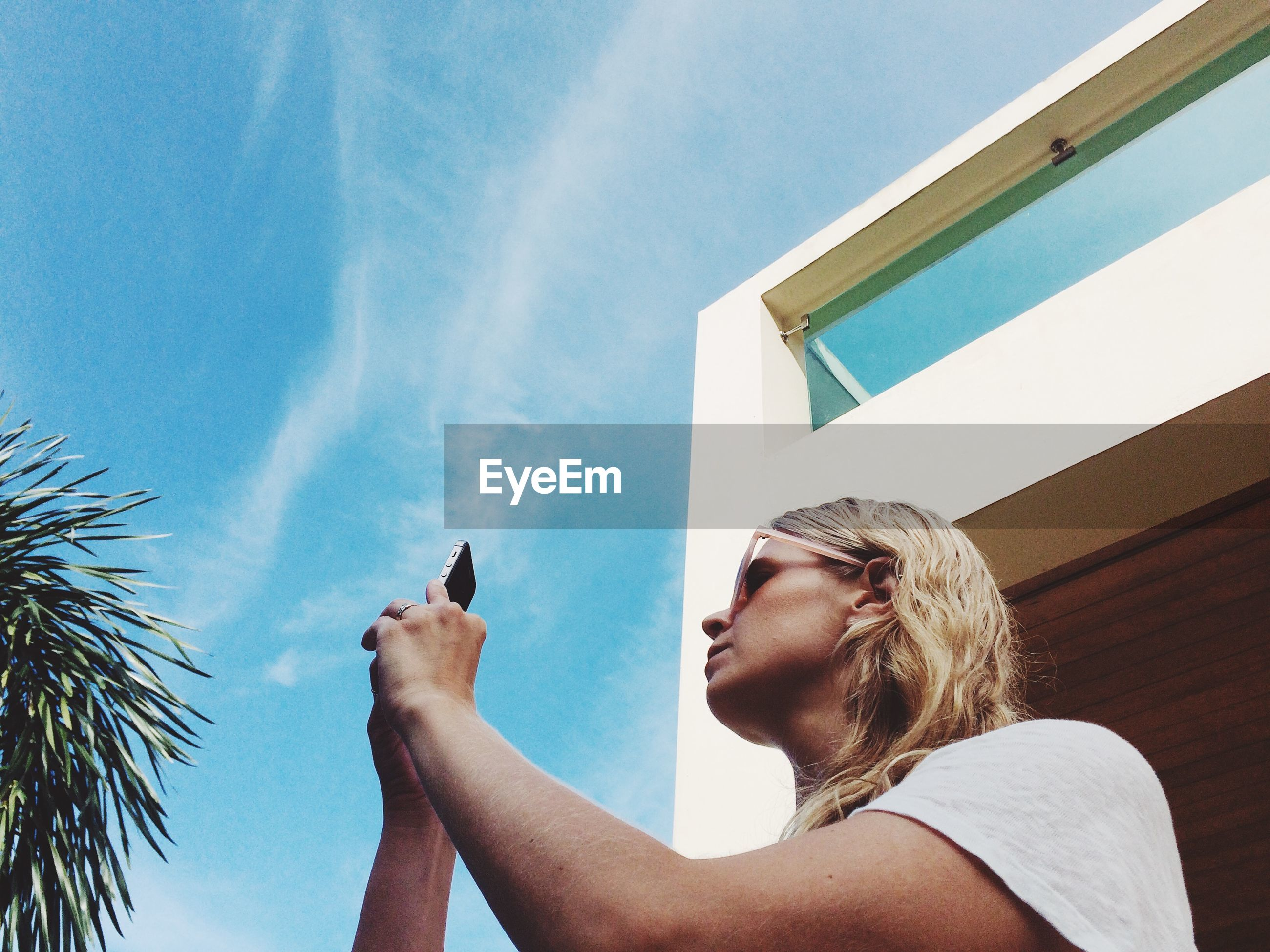 Low angle view of woman using mobile phone against sky