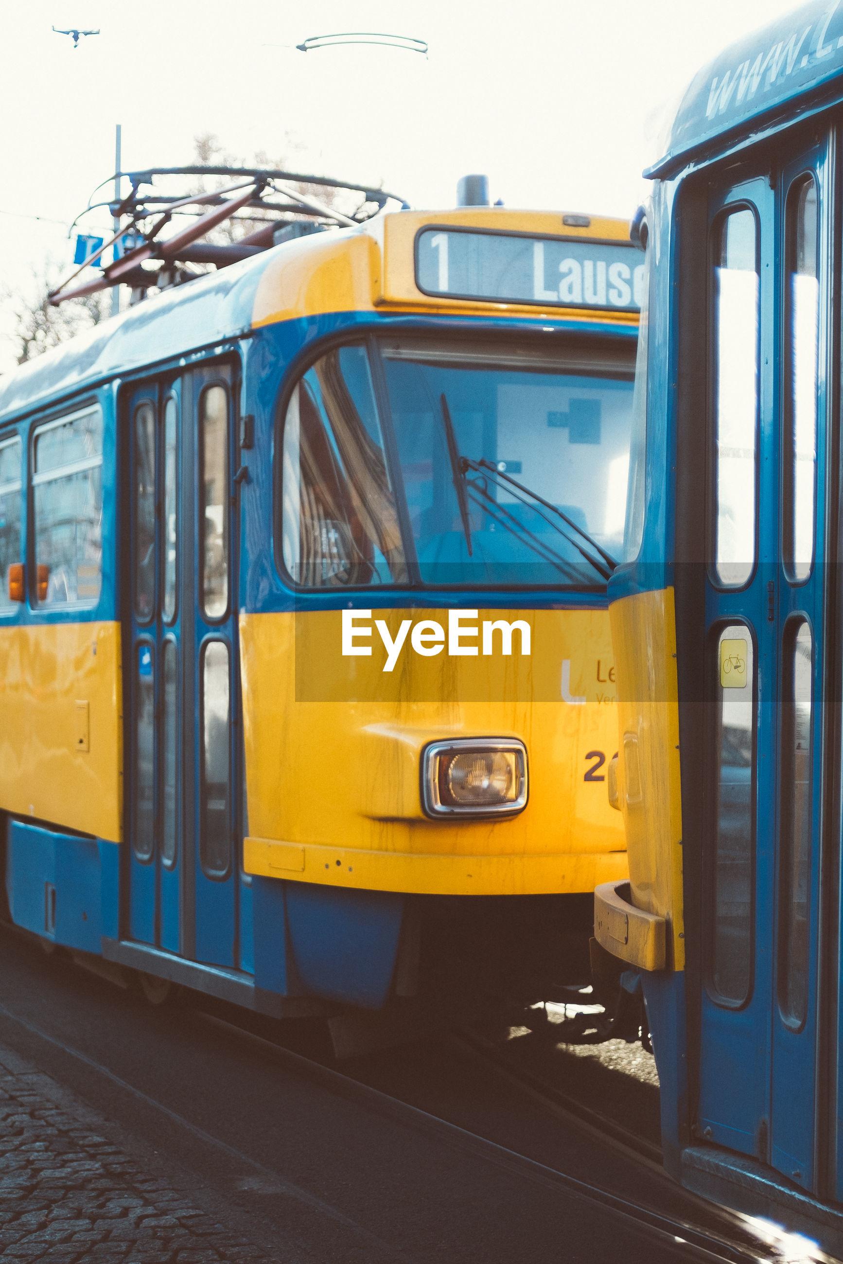 YELLOW TRAIN ON CITY IN RAILROAD TRACKS