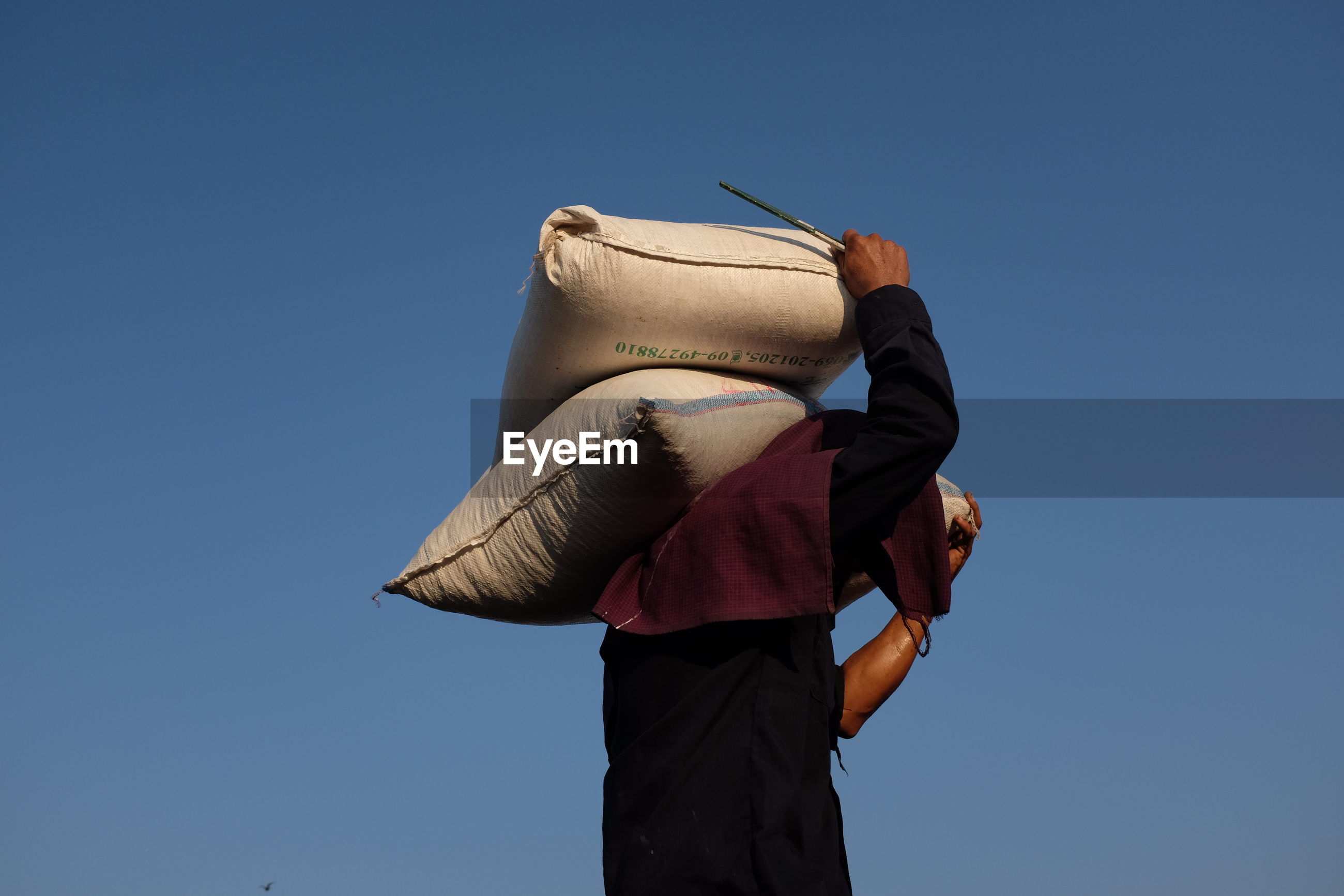Side view of man carrying sack while standing against blue sky