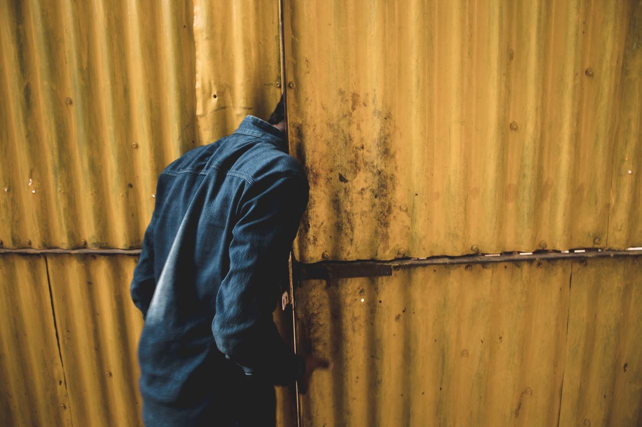 Rear view of teenage boy looking through old metallic gate