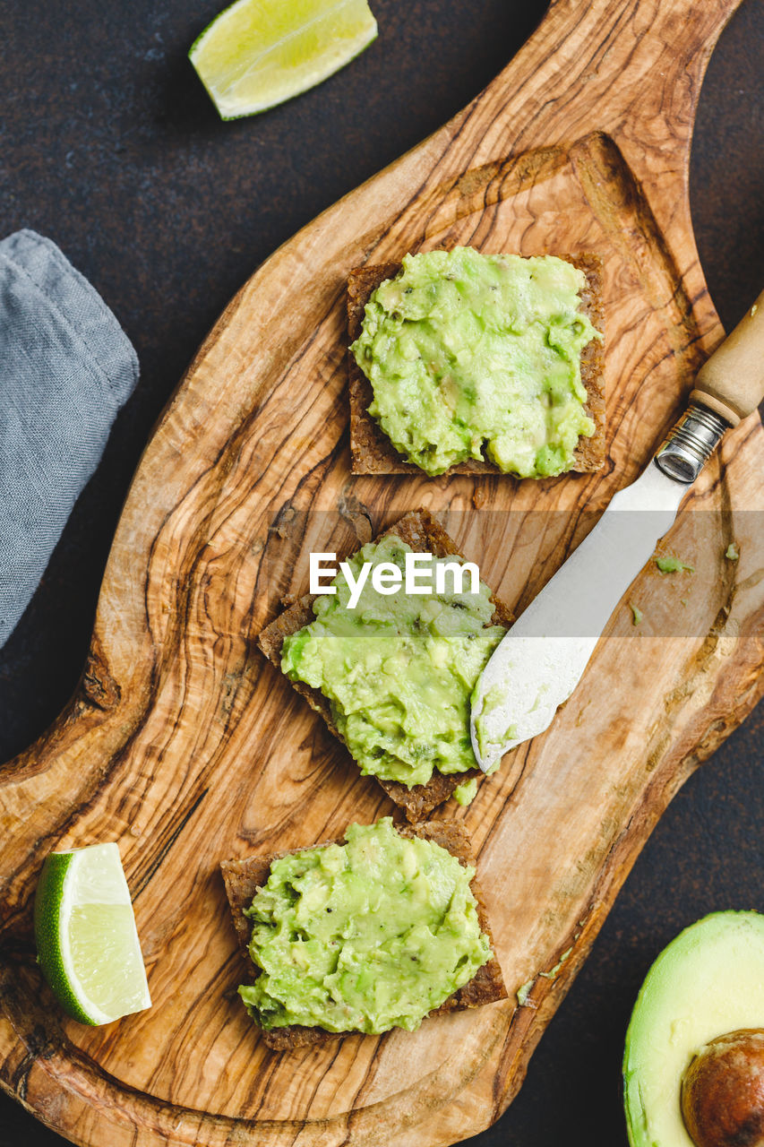 food and drink, food, healthy eating, freshness, wellbeing, fruit, high angle view, avocado, vegetable, cutting board, bread, still life, table, knife, wood - material, no people, indoors, guacamole, slice, directly above, dip, table knife, vegetarian food, chopped