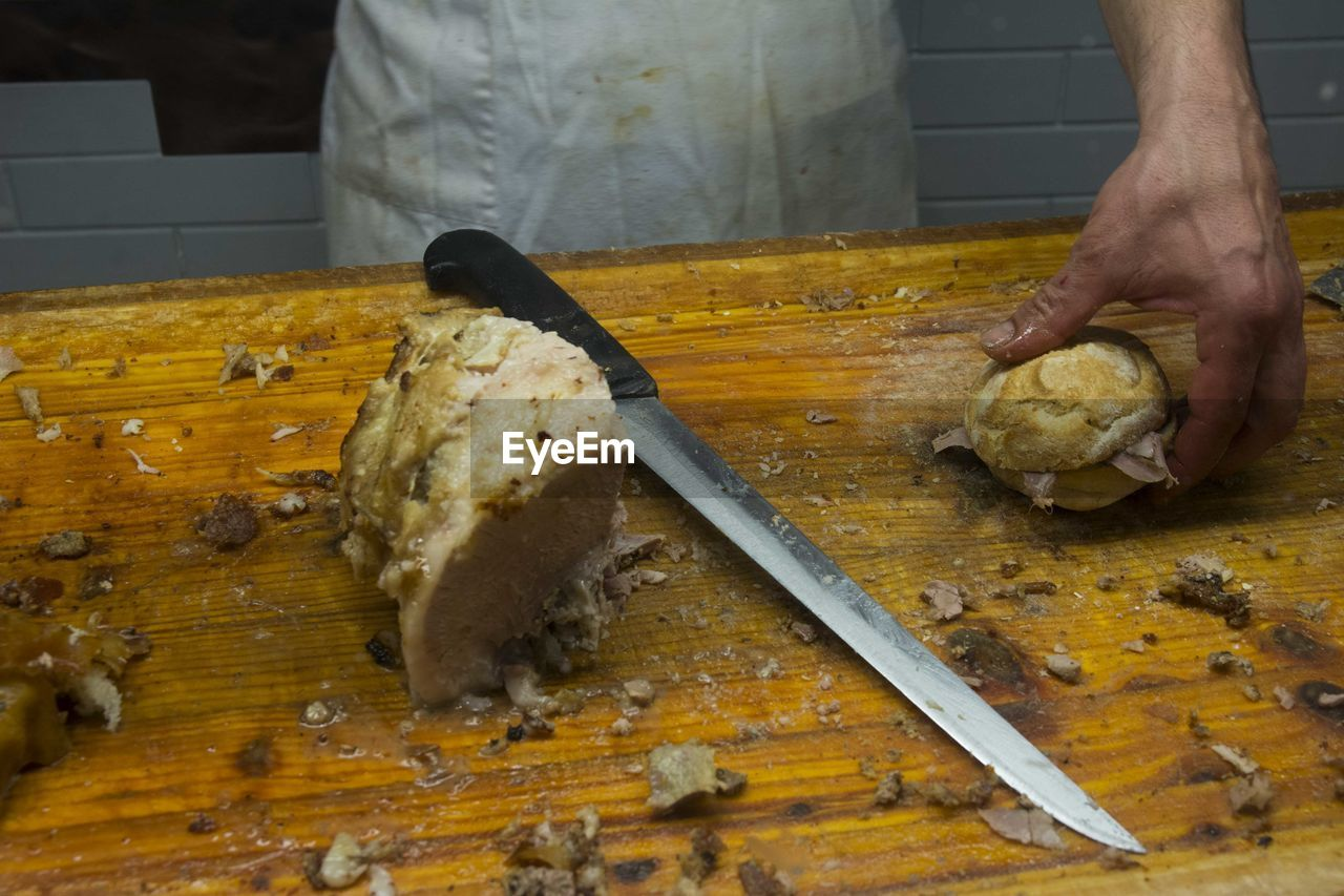 High angle view of hand holding burger along with knife