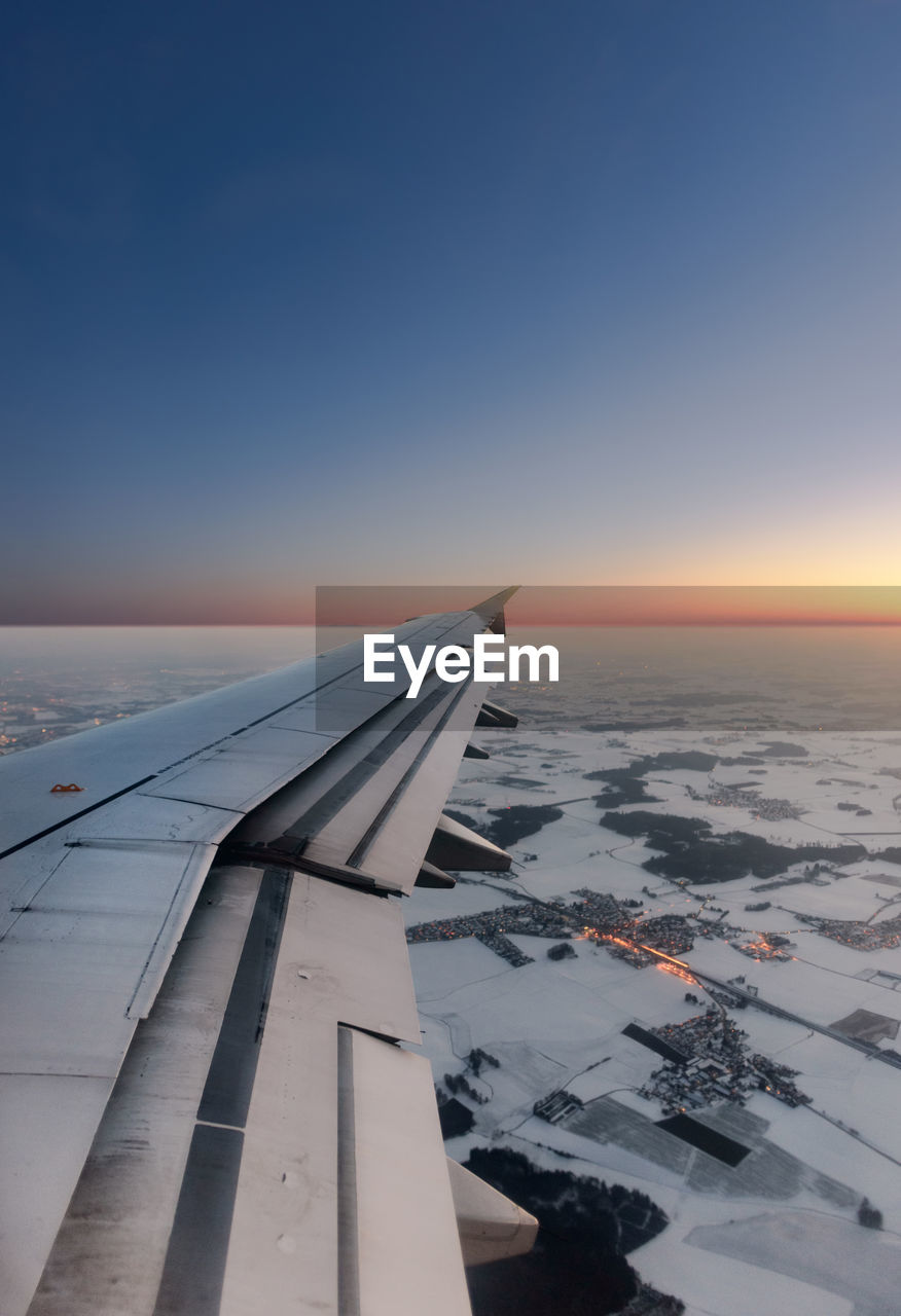 nature, airplane, scenics, aerial view, transportation, beauty in nature, sea, outdoors, mode of transport, no people, journey, aircraft wing, sunset, travel, tranquil scene, sky, air vehicle, tranquility, flying, blue, airplane wing, day, water, landscape, horizon over water, clear sky, cold temperature