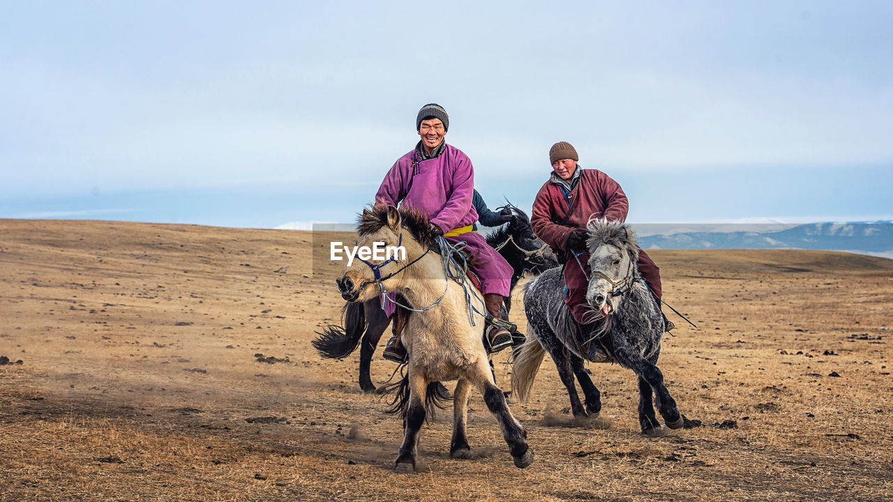 Men Horseback Riding On Landscape Against Sky