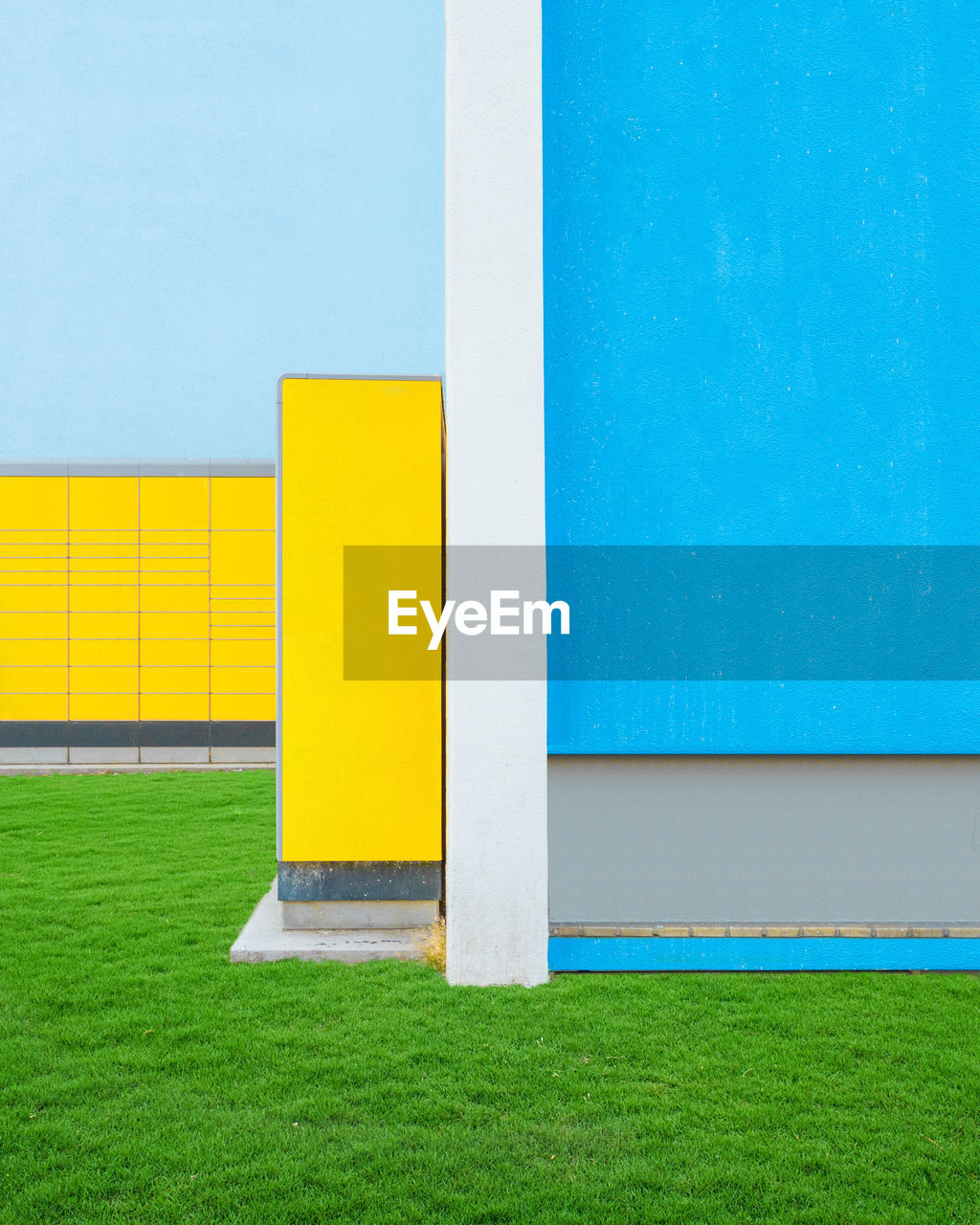 yellow, architecture, grass, wall - building feature, built structure, blue, green color, day, plant, no people, building exterior, copy space, outdoors, nature, multi colored, building, absence, white color, field, single line, blank