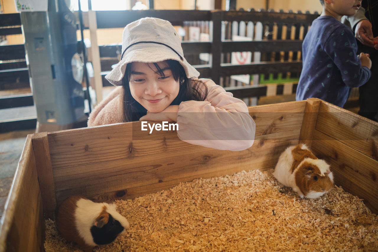Smiling woman looking at hamster in wooden box