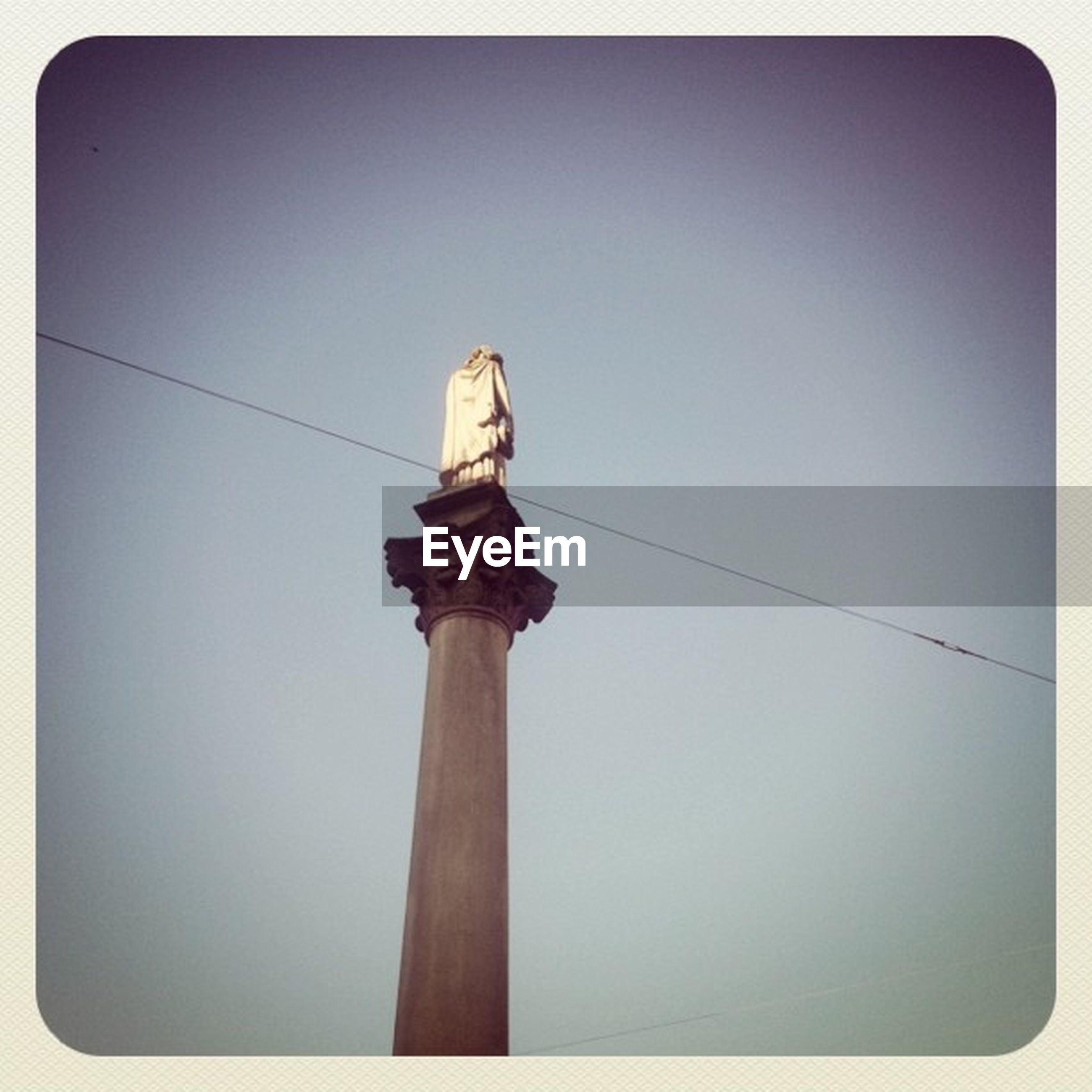 low angle view, transfer print, clear sky, auto post production filter, power line, copy space, built structure, architecture, electricity, pole, cable, sky, blue, technology, no people, high section, outdoors, building exterior, lighting equipment, day