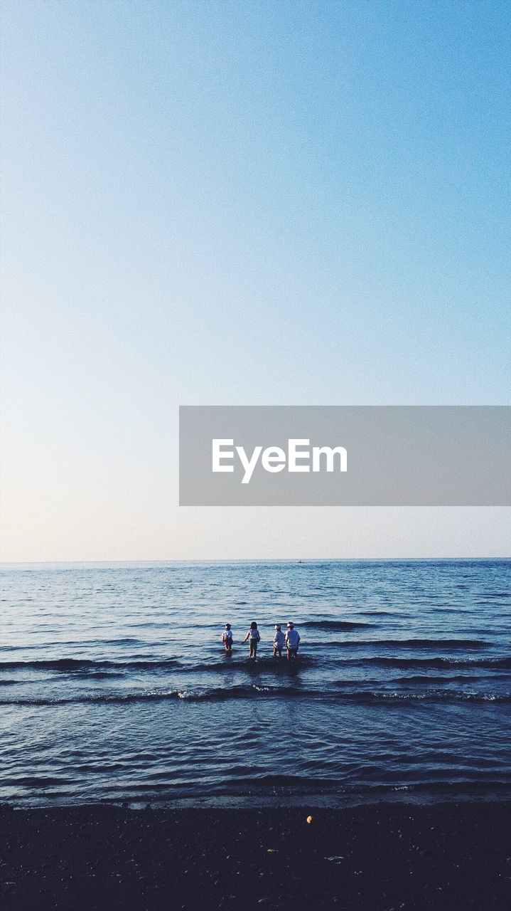 sea, water, sky, horizon, horizon over water, clear sky, copy space, group of people, scenics - nature, nature, beauty in nature, real people, leisure activity, land, beach, lifestyles, men, tranquility, blue, outdoors