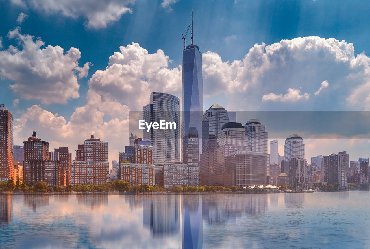 skyscraper, architecture, building exterior, city, water, built structure, tower, tall - high, waterfront, sky, modern, cloud - sky, cityscape, river, urban skyline, skyline, reflection, downtown district, travel destinations, no people, outdoors, tall, day