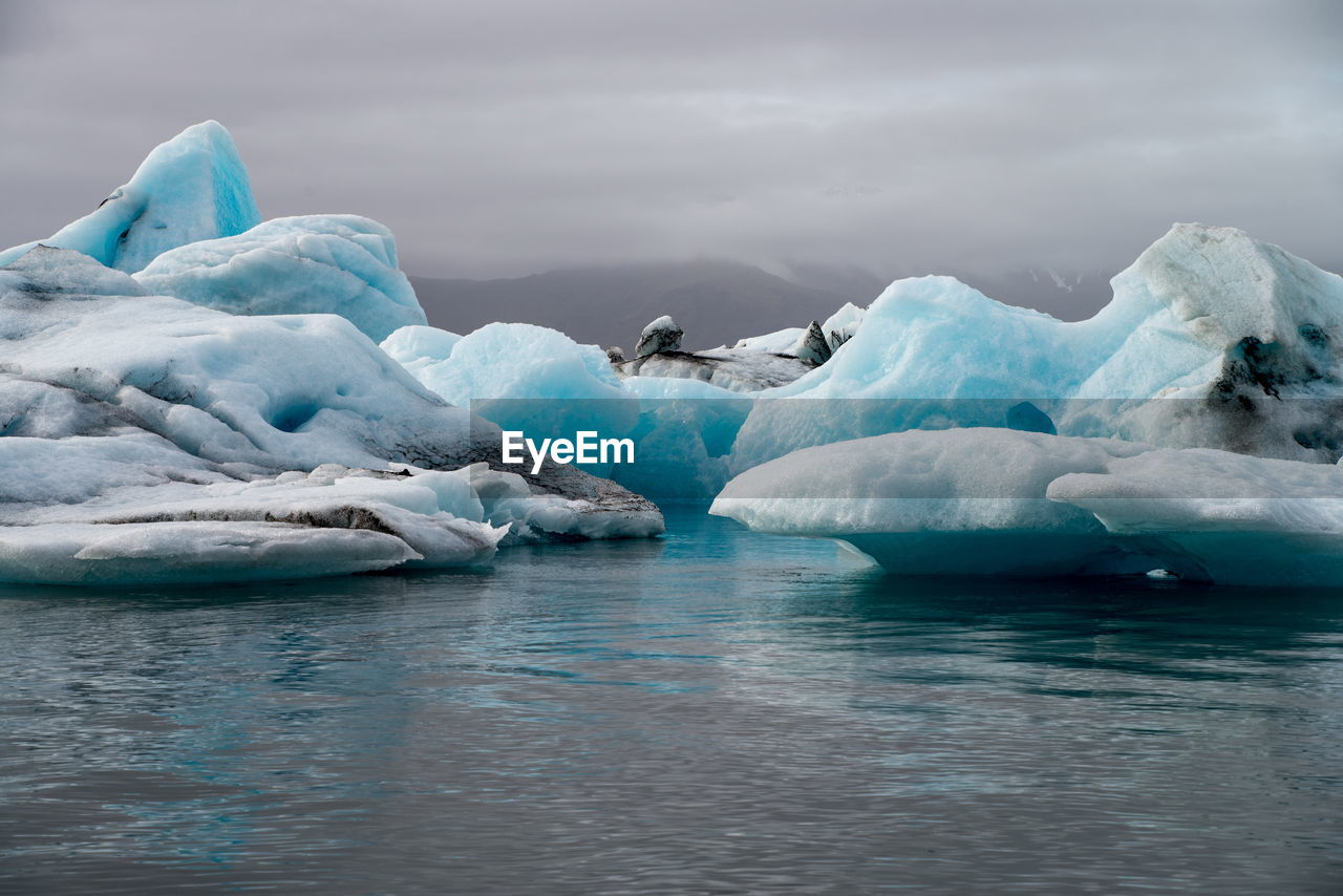 beauty in nature, iceberg, glacier, cold temperature, nature, ice, waterfront, frozen, scenics, water, no people, winter, tranquility, floating on water, outdoors, day, sky