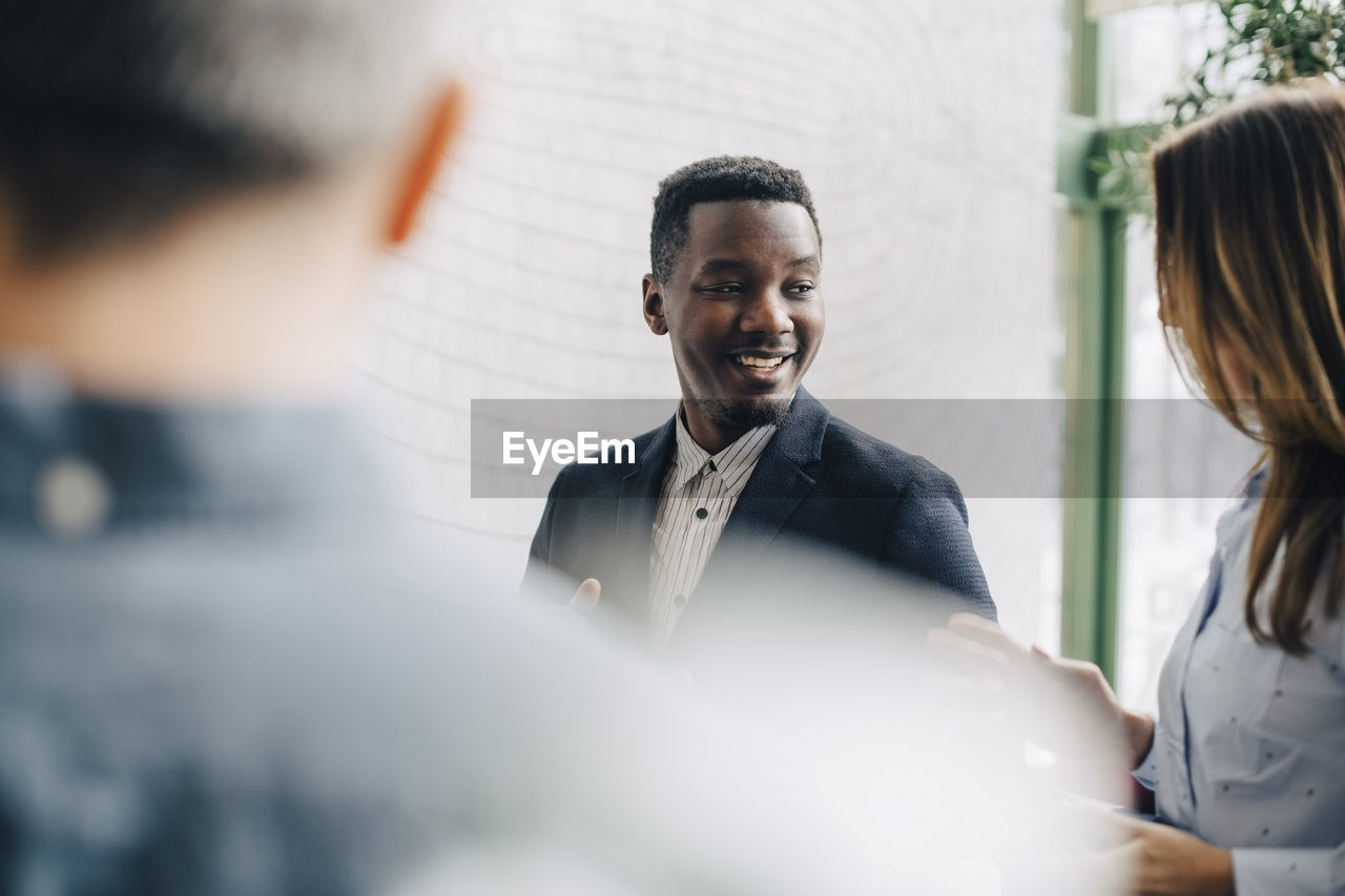 Smiling businessman discussing with coworkers at conference