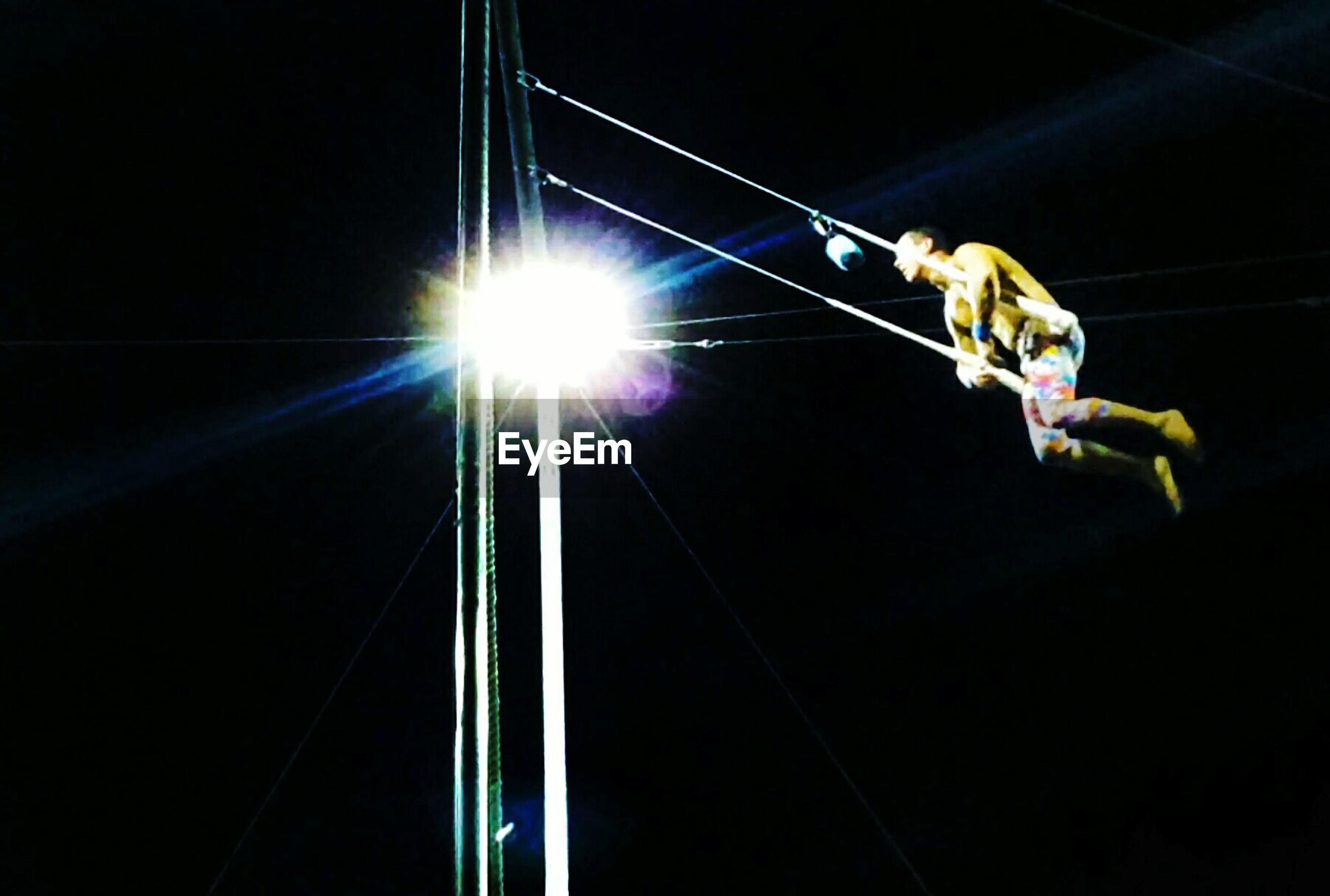 low angle view, night, illuminated, electricity, lighting equipment, light - natural phenomenon, street light, lens flare, glowing, clear sky, blue, transportation, cable, copy space, outdoors, no people, speed, connection, rope, motion