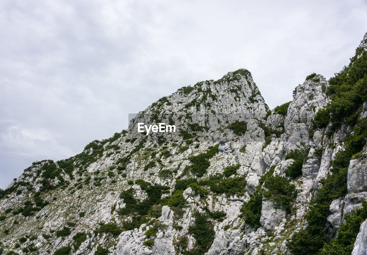 sky, beauty in nature, rock, nature, cloud - sky, low angle view, mountain, rock - object, day, tranquility, no people, solid, cold temperature, rock formation, plant, tranquil scene, snow, outdoors, mountain peak, formation, high