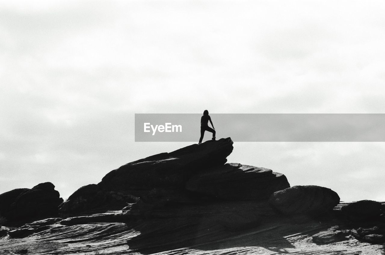 Silhouette Woman Standing On Rock Against Sky