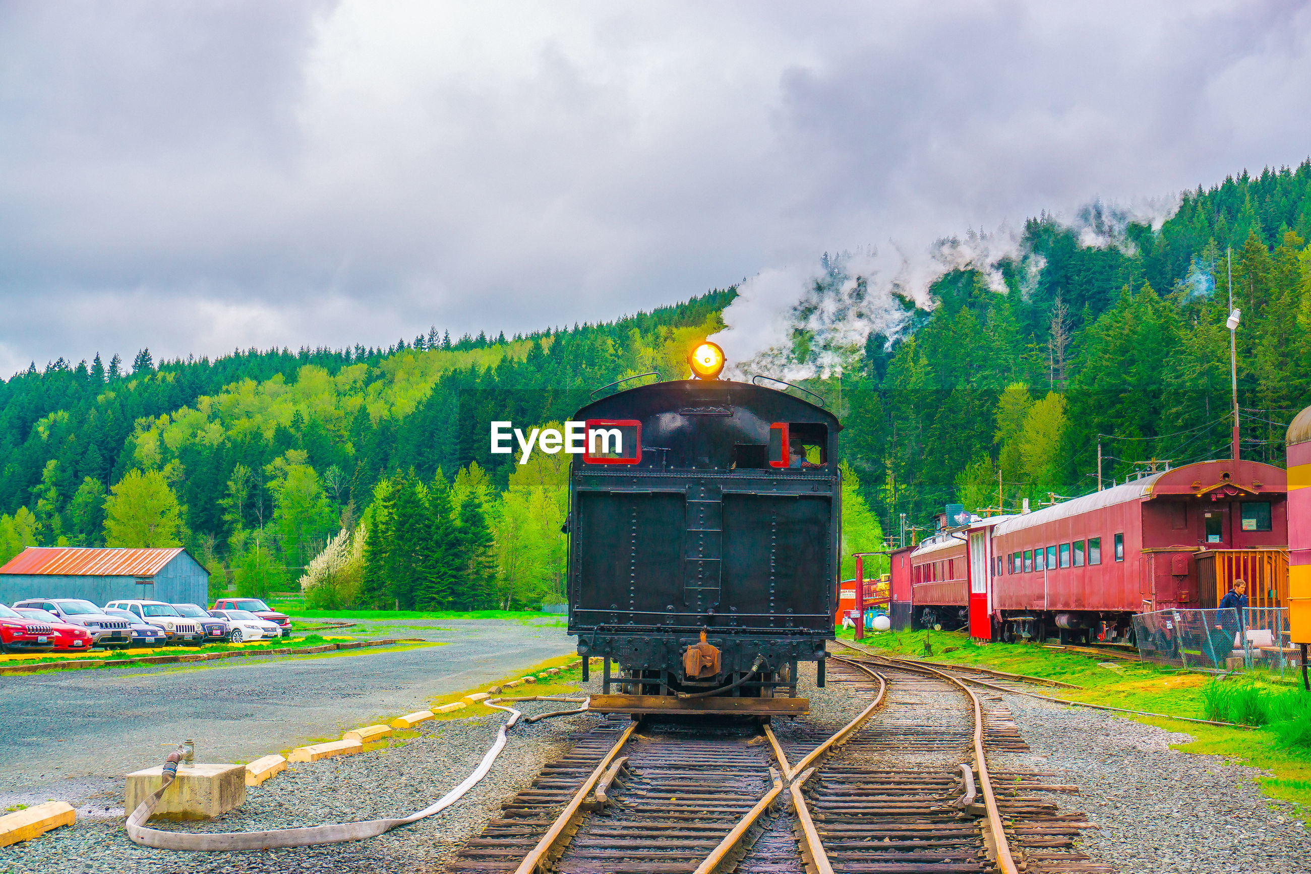 Trains on railroad track against cloudy sky