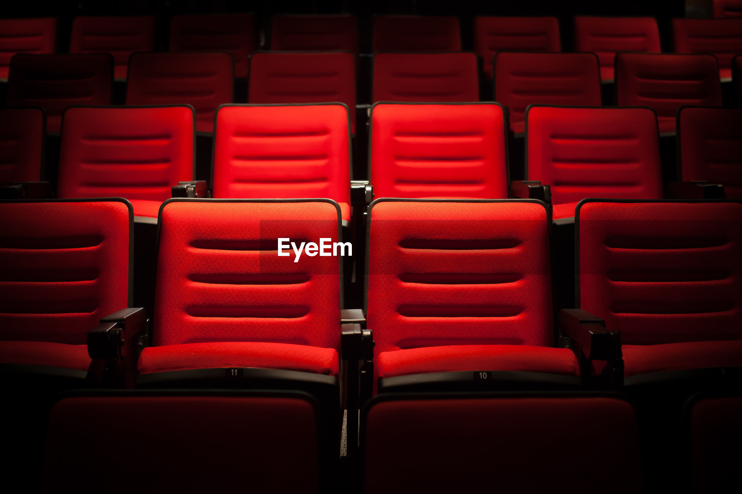 Full frame shot of empty red seats in auditorium