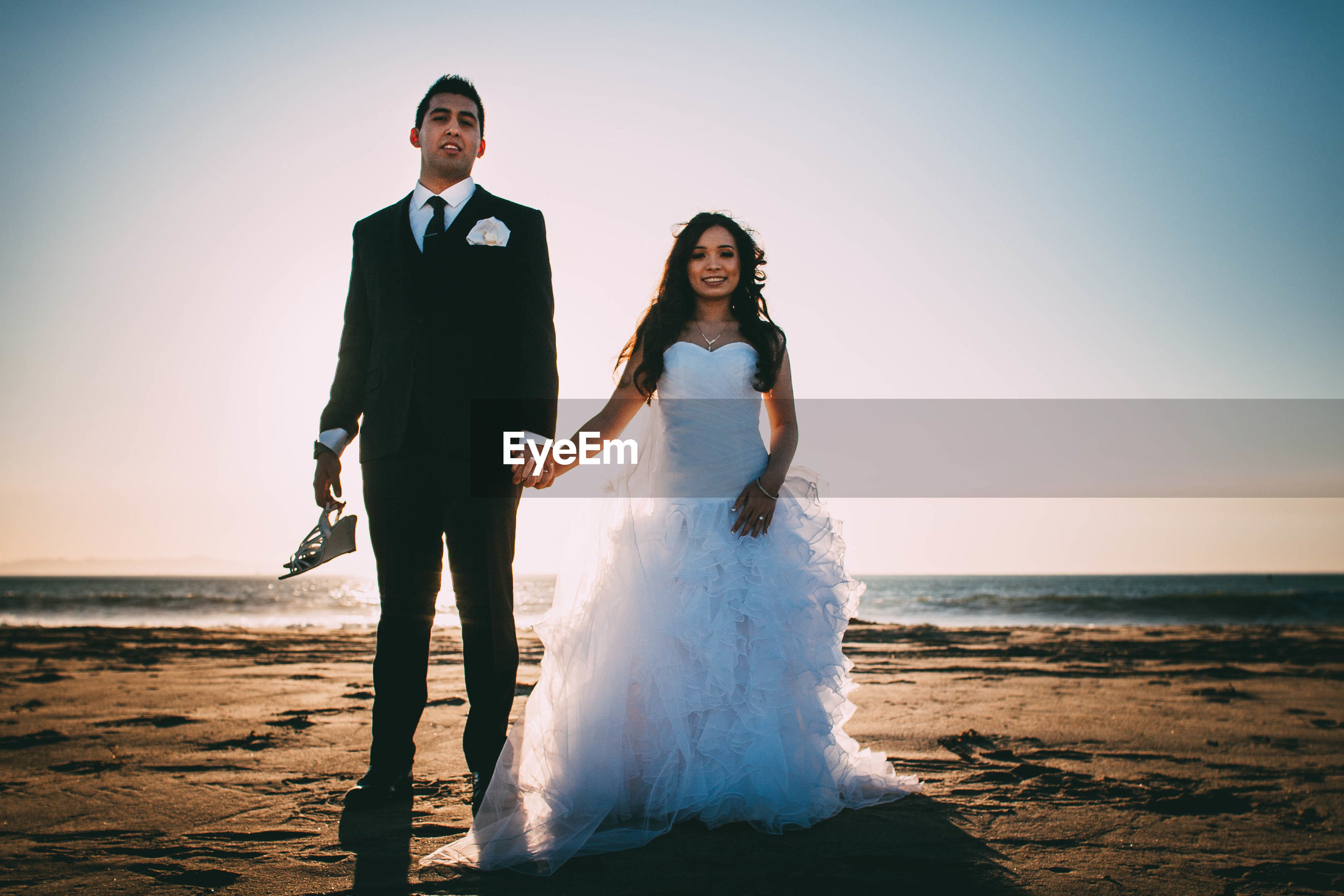 sea, real people, wedding, beach, bride, wedding dress, love, front view, two people, young women, standing, full length, sunset, togetherness, young adult, wife, nature, husband, outdoors, horizon over water, young men, looking at camera, sky, lifestyles, groom, couple - relationship, clear sky, scenics, bonding, life events, bridegroom, water, portrait, well-dressed, day, beauty in nature, people