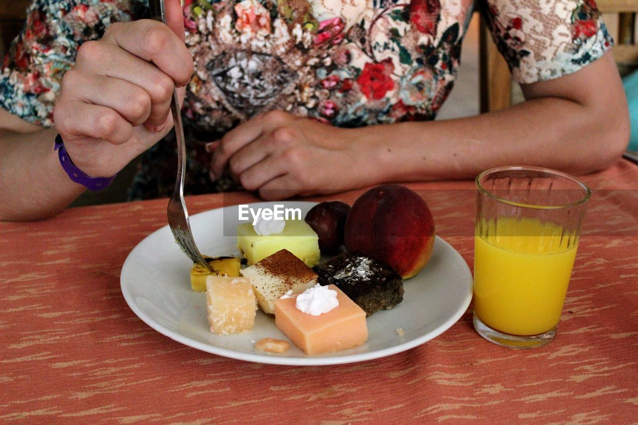 food and drink, table, food, one person, real people, human hand, plate, holding, freshness, midsection, drink, healthy eating, lifestyles, indoors, ready-to-eat, sitting, close-up, human body part, day, people