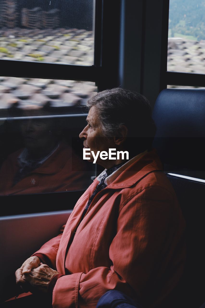real people, sitting, one person, senior adult, window, lifestyles, looking, indoors, adult, senior women, casual clothing, males, mode of transportation, leisure activity, men, looking away, home interior, car, motor vehicle, mature men, contemplation