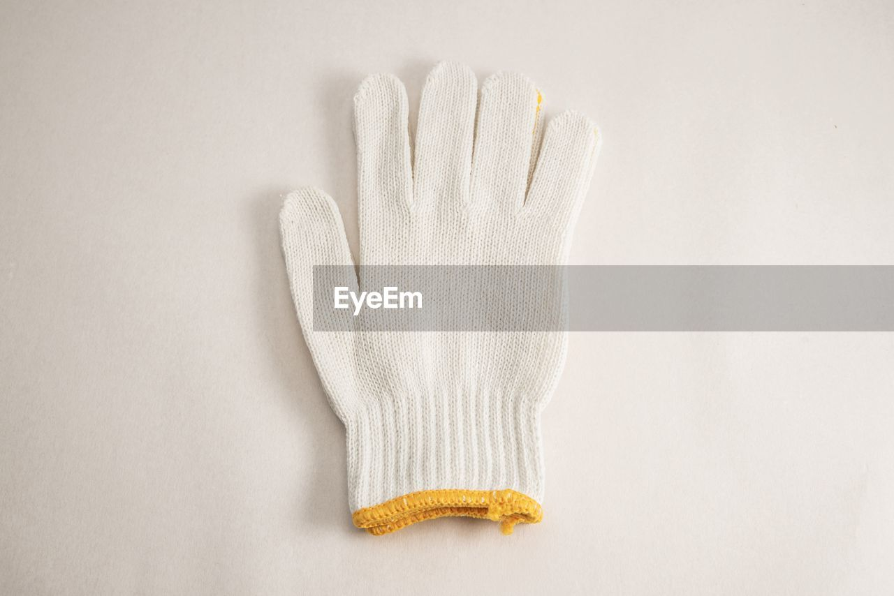 studio shot, glove, indoors, white background, white color, human hand, still life, high angle view, protective glove, close-up, copy space, protection, protective workwear, textile, winter, people, directly above, warm clothing, clean