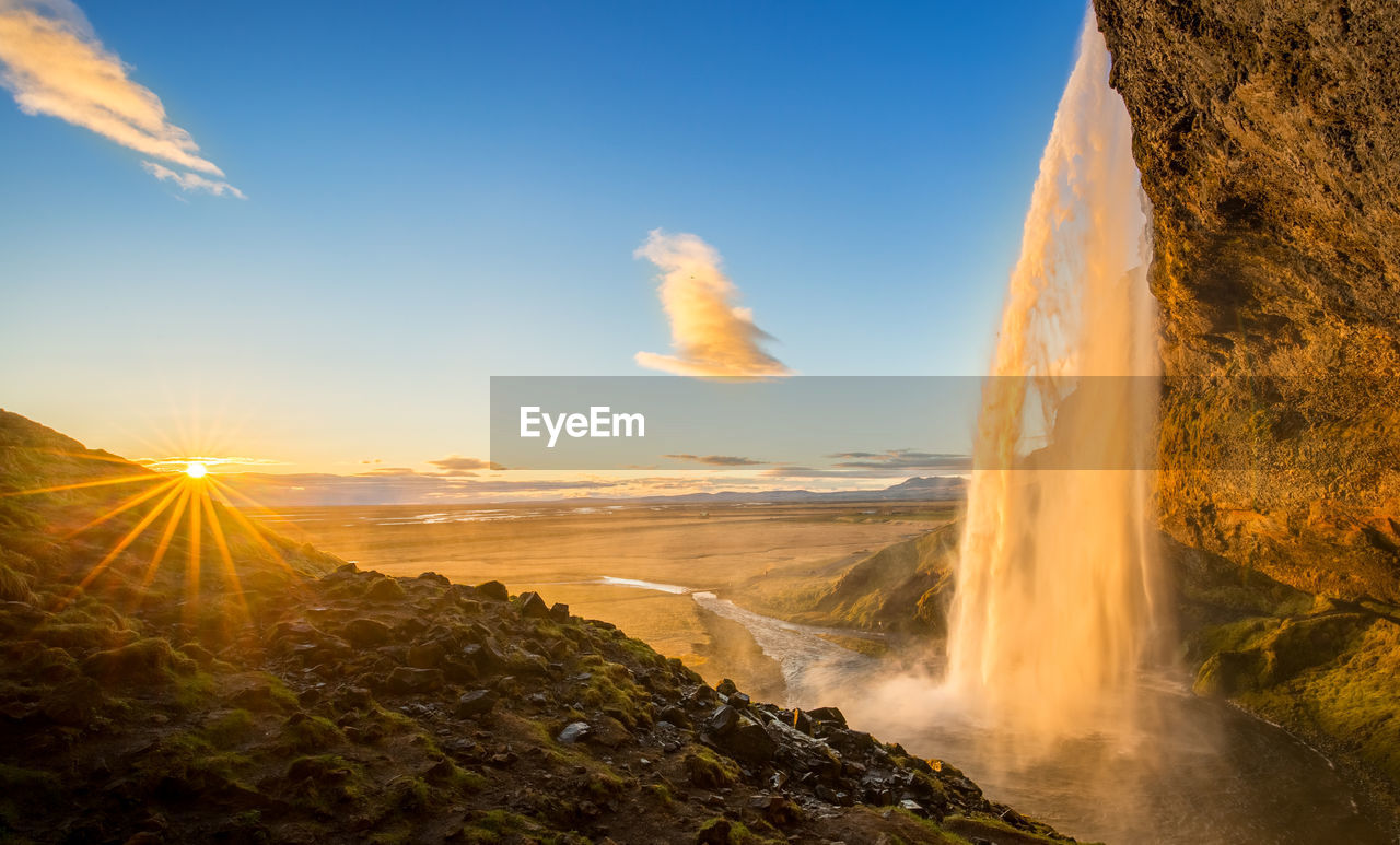 PANORAMIC VIEW OF WATERFALL AGAINST SKY DURING SUNSET
