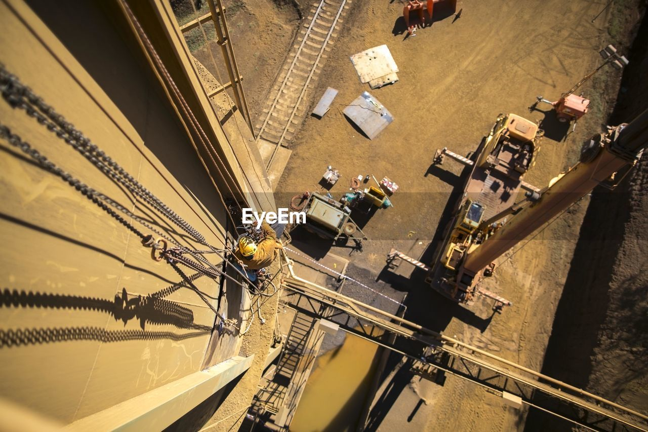 high angle view, real people, occupation, architecture, transportation, industry, day, group of people, built structure, men, working, outdoors, machinery, incidental people, construction industry, mode of transportation, sunlight, city, nature
