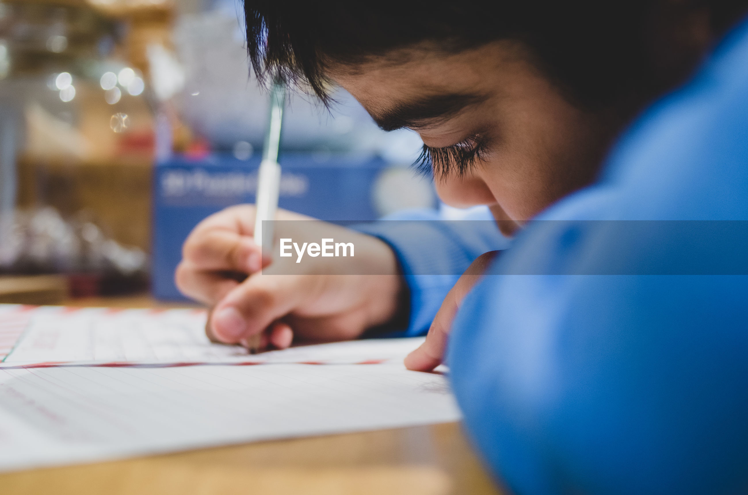 Close-up of boy writing on paper at table
